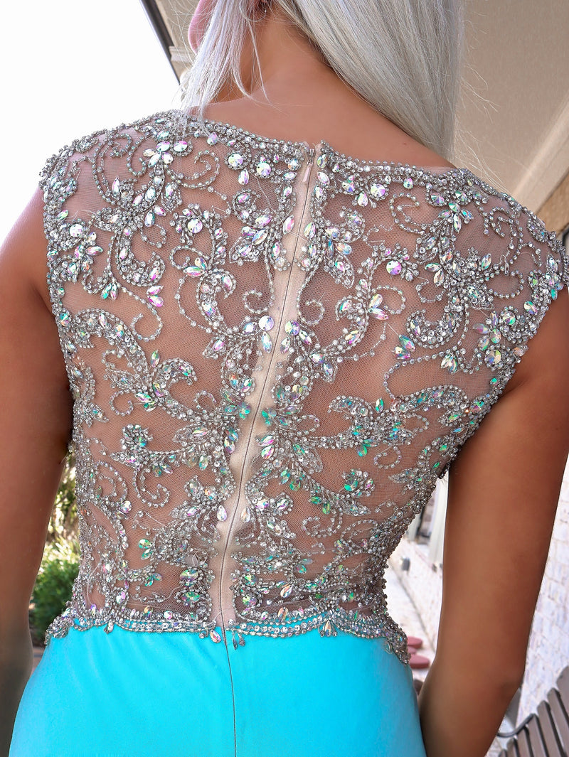 Closeup of back of Model in a gown that's Simple elegance with a sexy flair is what this gorgeous jersey style gown is all about! And it's at Rsvp Prom and Pageant, your source for the HOTTEST Prom and Pageant Dresses and exclusive evening gowns and located in Atlanta, Georgia!