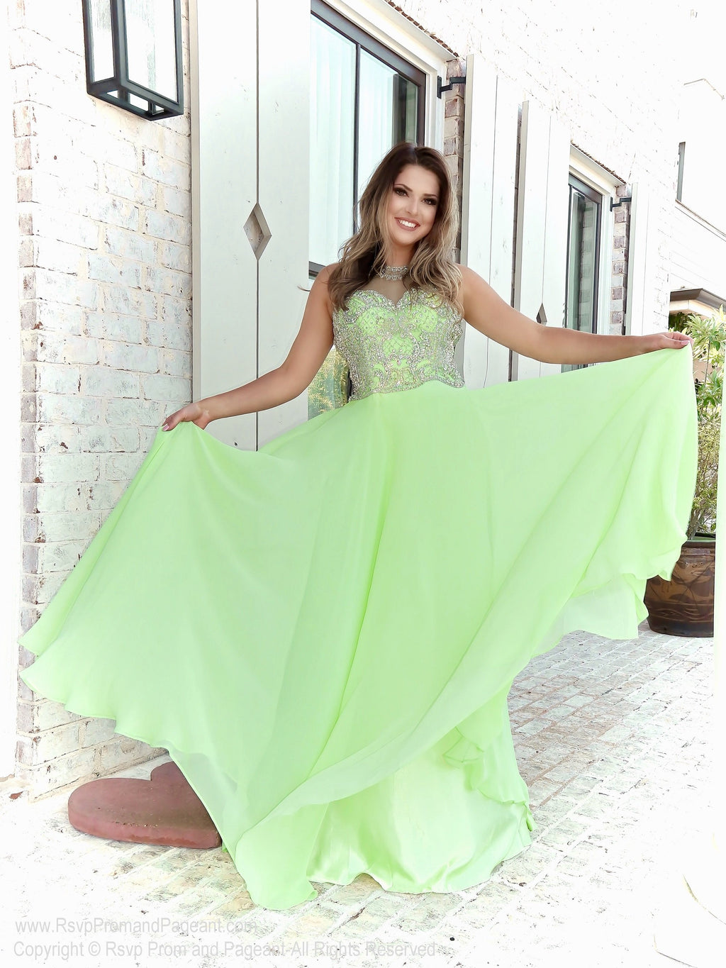 Brunette model in in this gorgeous pastel green prom dress with an open back and flowing chiffon skirt! So elegant and it's at Rsvp Prom and Pageant, your source for the HOTTEST Prom and Pageant Dresses and exclusive evening gowns and located in Atlanta, Georgia!