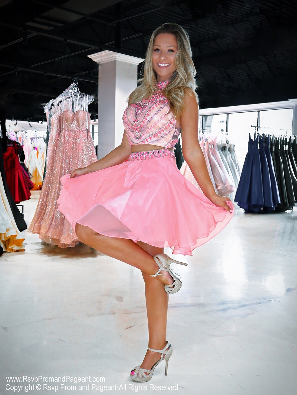 Model standing on one leg in the Cute Coral Two Piece Homecoming Dress with Beaded Crop Top at Rsvp Prom and Pageant, which is the largest prom brand and located in metro Atlanta, Georgia