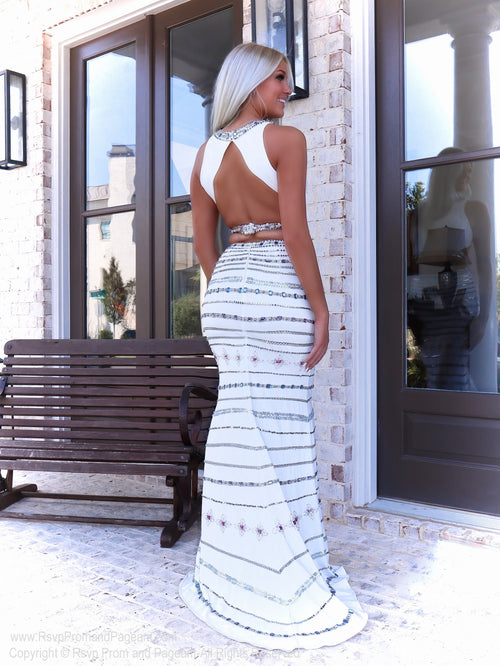 Back of Beautiful model in a white two piece prom dress of which the skirt is completely beaded with turquoise and blue stones!  And it's at Rsvp Prom and Pageant, your source for the HOTTEST Prom and Pageant Dresses and exclusive evening gown located in Atlanta, Georgia!