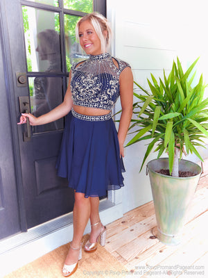Pretty blonde standing at door in beautifully Embellished Navy Two Piece Homecoming Dress at Rsvp Prom and Pageant, the largest prom dress store, Atlanta, Georgia