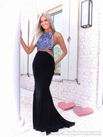 Model in a black flirty jersey gown with a high neckline with extravagant detailing and side cut outs. Ad it's at Rsvp Prom and Pageant, your source for the HOTTEST Prom and Pageant Dresses and exclusive evening gowns and located in Atlanta, Georgia!