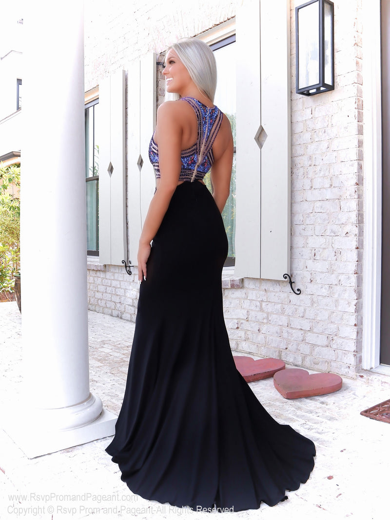 Back of model in a black flirty jersey gown with a high neckline with extravagant detailing and side cut outs. Ad it's at Rsvp Prom and Pageant, your source for the HOTTEST Prom and Pageant Dresses and exclusive evening gowns and located in Atlanta, Georgia!