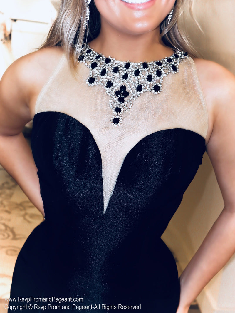 Closeup of Model looking like the Queen at the Ball in this jaw dropping black couture evening gown with its beaded neckline and back and long ruffled train! And it's at Rsvp Prom and Pageant, your source for the HOTTEST Prom and Pageant Dresses and Exclusive Evening Gowns and located in Atlanta, Georgia!