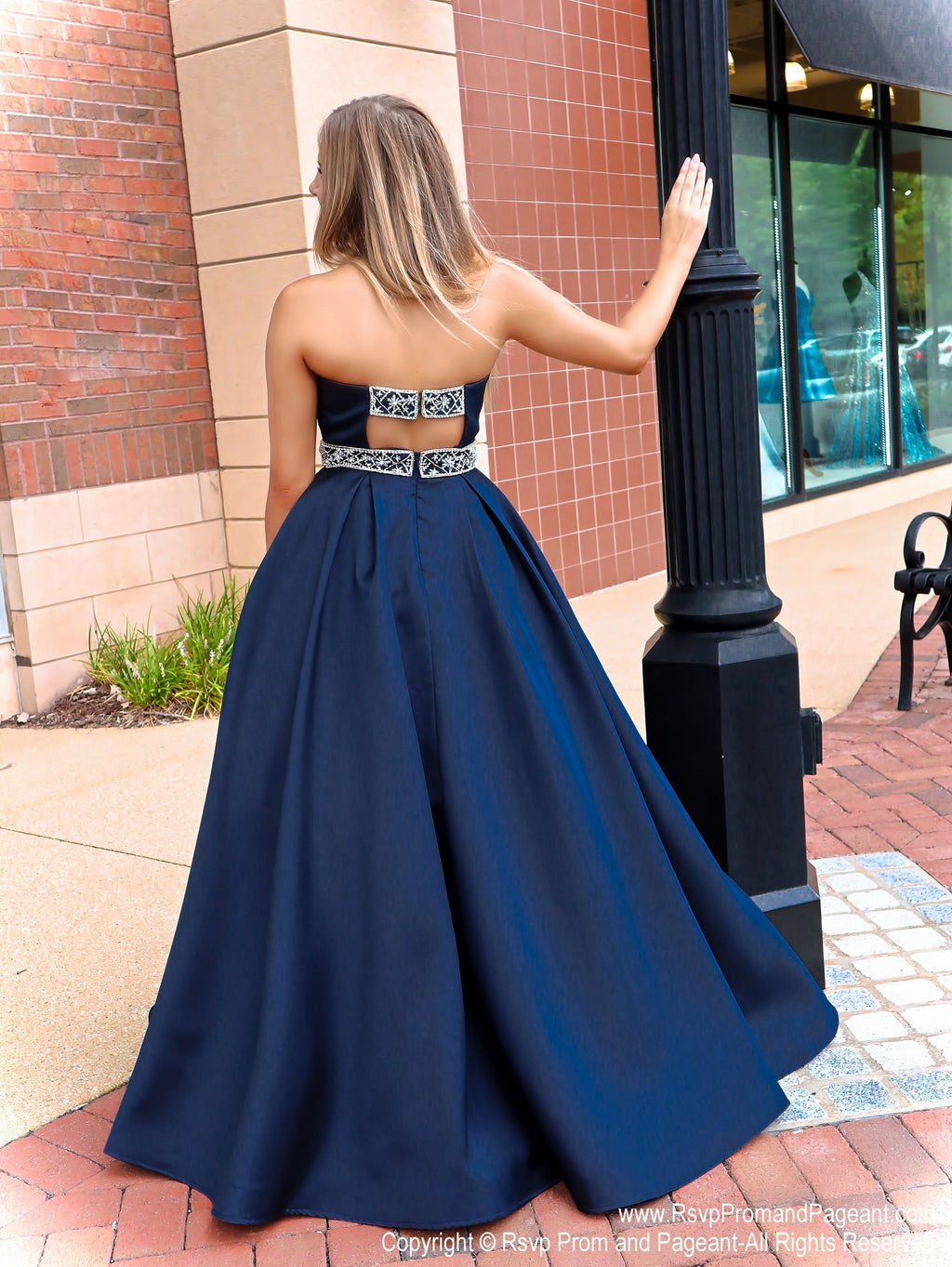 Back of model in the prettiest ball gown you've ever seen with its halter neckline and beautifully detailed back straps! And it's at Rsvp Prom and Pageant, your source for the HOTTEST Prom and Pageant Dresses and Exclusive Evening Gowns and located in Atlanta, Georgia!