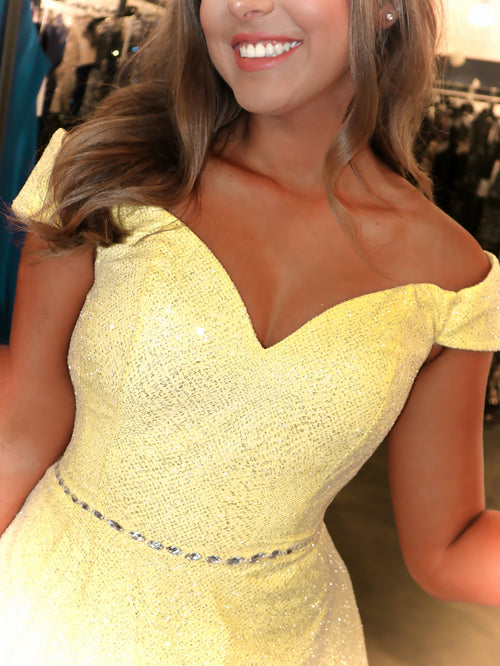 Closeup of Model sparkling under the lights in this pretty yellow, off-the-shoulder A-line Prom Dress! And its at RSVP Prom and Pageant, your source for the HOTTEST Prom and Pageant Dresses and Exclusive Evening Gowns and located in Atlanta, Georgia!
