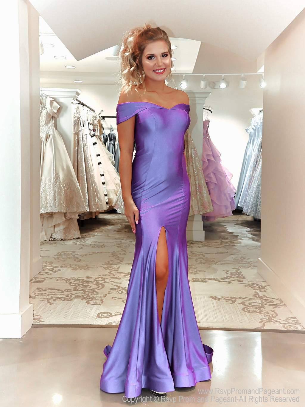 Model in a simple violet of the shoulder fitted gown with a slit. And it's at Rsvp Prom and Pageant, your source for the HOTTEST Prom and Pageant Dresses and Exclusive Evening Gowns and located in Atlanta, Georgia!