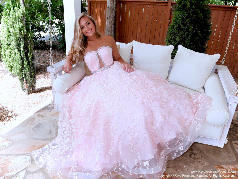 Blonde girl sitting in a absolutely stunning lace ball gown features a strapless sweetheart neckline and a cut out in the bodice! And it's at Rsvp Prom and Pageant, your source for the HOTTEST Prom and Pageant Dresses, located in Atlanta, Georgia!