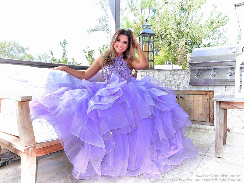 Seated Model in a beautiful lilac gown with its intricately laced high neckline bodice, low scooped back and its voluminous asymmetrically layered and tiered tulle skirt. This is THE dress and it's at Rsvp Prom and Pageant, your source for the HOTTEST Prom and Pageant dresses and Exclusive Evening Gowns and located in Atlanta, Georgia!