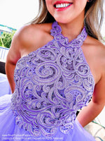 Closeup of Model in a beautiful lilac gown with its intricately laced high neckline bodice, low scooped back and its voluminous asymmetrically layered and tiered tulle skirt. This is THE dress and it's at Rsvp Prom and Pageant, your source for the HOTTEST Prom and Pageant dresses and Exclusive Evening Gowns and located in Atlanta, Georgia!