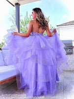 Back of Model in a beautiful lilac gown with its intricately laced high neckline bodice, low scooped back and its voluminous asymmetrically layered and tiered tulle skirt. This is THE dress and it's at Rsvp Prom and Pageant, your source for the HOTTEST Prom and Pageant dresses and Exclusive Evening Gowns and located in Atlanta, Georgia!
