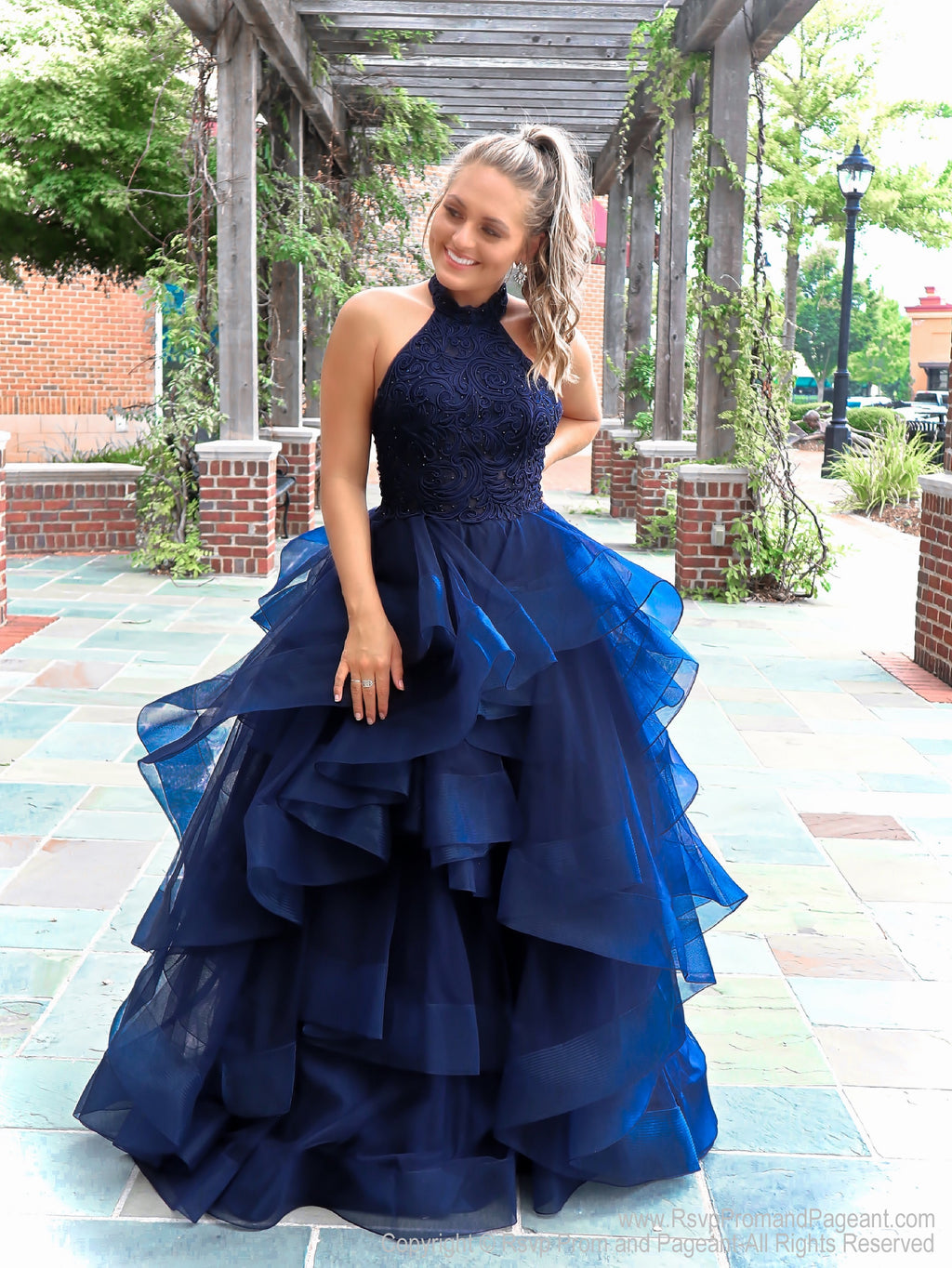 Model in this gorgeous navy gown! The bodice is beautifully embroidered and features a halter top. And it's at Rsvp Prom and Pageant, your source for the Hottest Prom and Pageant Dresses and exclusive evening gowns and located in Atlanta, Georgia!