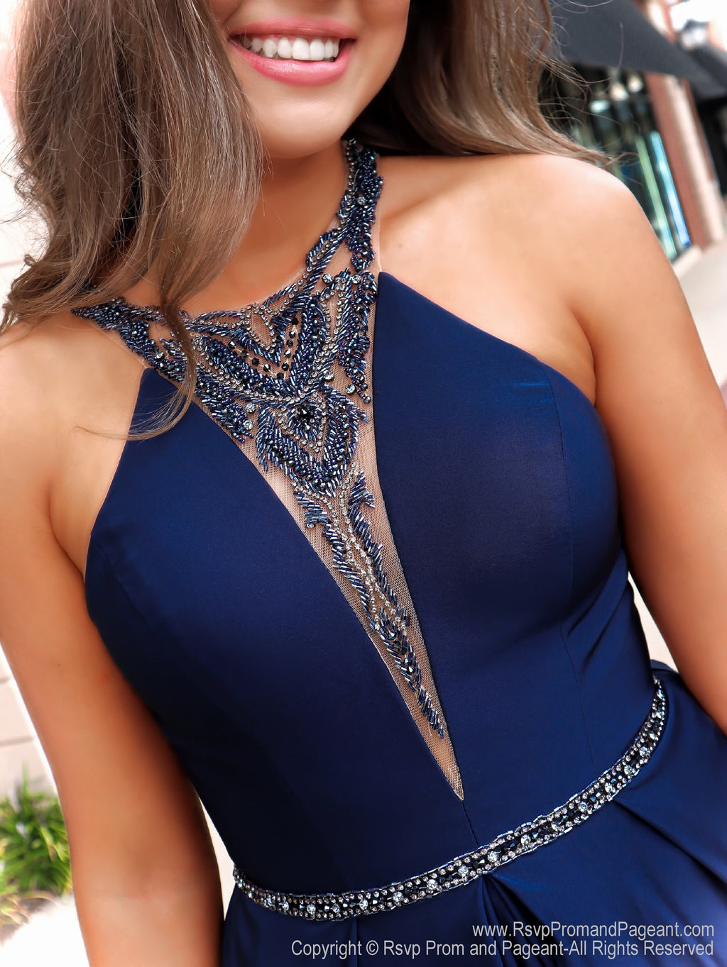 Closeup of model in a magnificent navy ball gown featuring a high neckline and beautifully detailed beading on the back! And it's at Rsvp Prom and Pageant, your source for the HOTTEST Prom and Pageant Dresses and Exclusive Evening Gowns and located in Atlanta  Georgia!