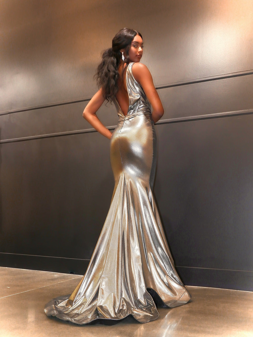 African American model looking over her shoulder in this sexy Silver fit and flare evening gown!  And its at RSVP Prom and Pageant, your source for the HOTTEST Prom and Pageant Dresses and exclusive evening gowns and located in Atlanta, Georgia.