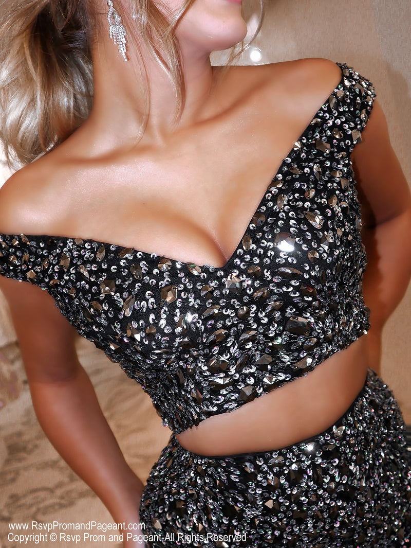 Closeup of Model in a glamorous black two piece sparkling from head to toe completely covered with sequins. The feathers on the skirt give it an even more sophisticated look! And it's at Rsvp Prom and Pageant, your source for the HOTTEST Prom and Pageant Dresses and exclusive evening gowns and located in Atlanta, Georgia!