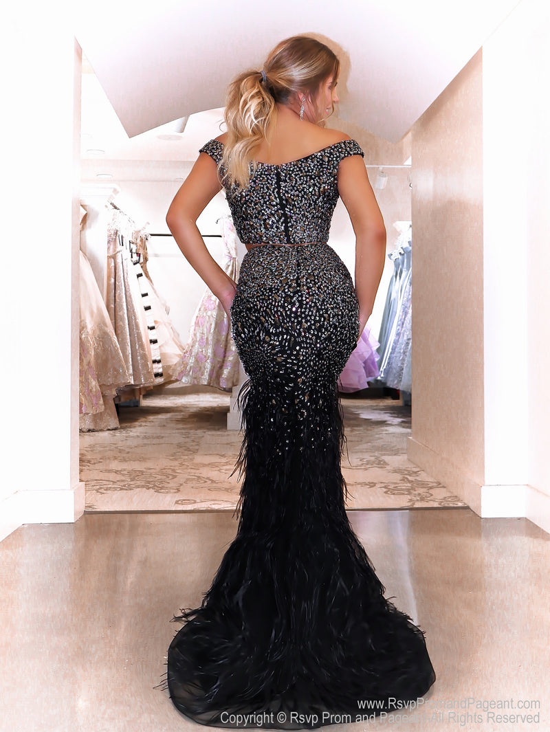 Back of Model in a glamorous black two piece sparkling from head to toe completely covered with sequins. The feathers on the skirt give it an even more sophisticated look! And it's at Rsvp Prom and Pageant, your source for the HOTTEST Prom and Pageant Dresses and exclusive evening gowns and located in Atlanta, Georgia!