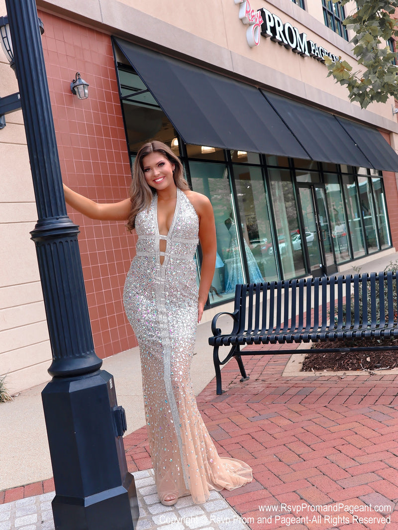 Model in front of Rsvp store in Talk about a show stopper!! No doubt, you will wow the crowd in this gorgeous evening fully detailed with iridescent stones! It also features a low cut back and a halter neckline! And it's at Rsvp Prom and Pageant, your source for the HOTTEST Prom, Pageant and evening gowns, Atlanta, Georgia!