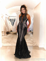 Model in a black sophisticated gown featuring lace all over and a high choker neckline and open back! And it's at Rsvp Prom and Pageant, your source for the HOTTEST Prom and Pageant Dresses and Exclusive Evening Gowns and located in Atlanta, Georgia!