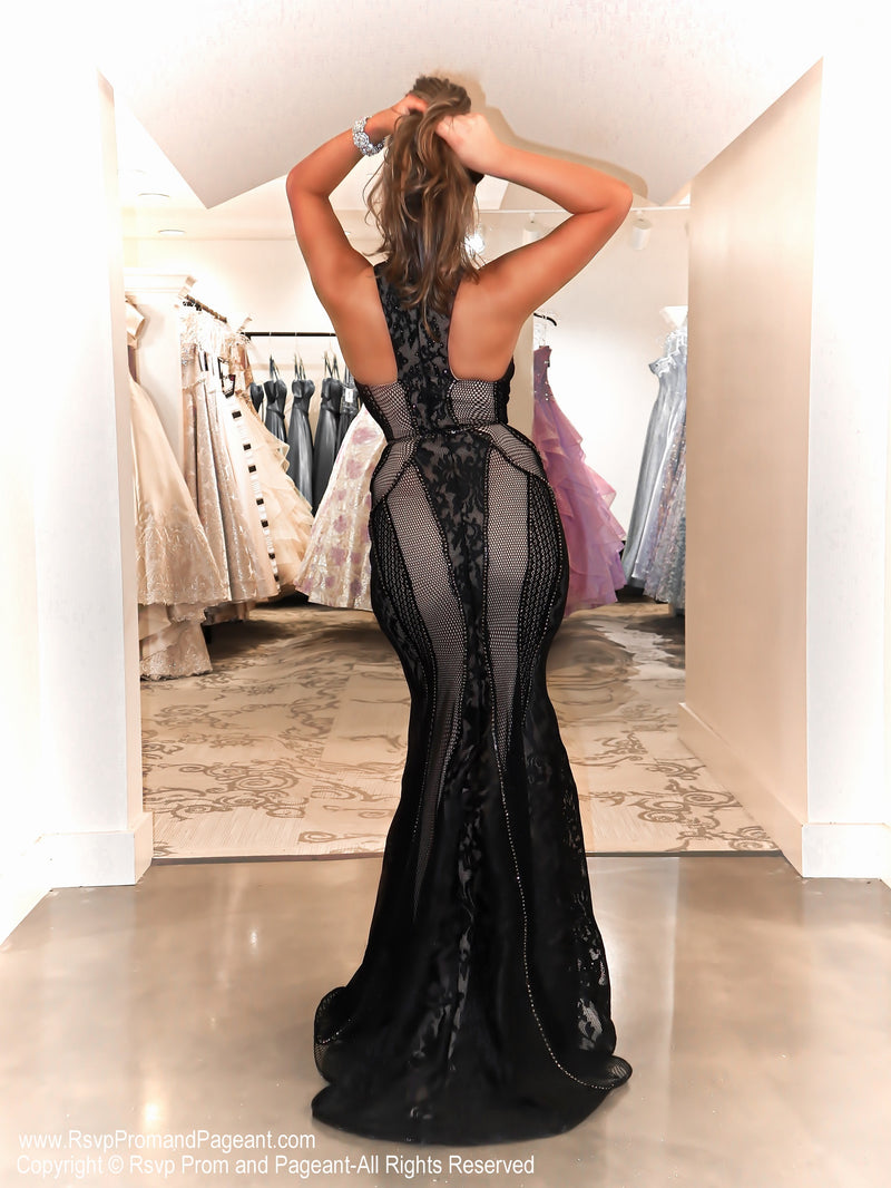 Back of Model in a black sophisticated gown featuring lace all over and a high choker neckline and open back! And it's at Rsvp Prom and Pageant, your source for the HOTTEST Prom and Pageant Dresses and Exclusive Evening Gowns and located in Atlanta, Georgia!
