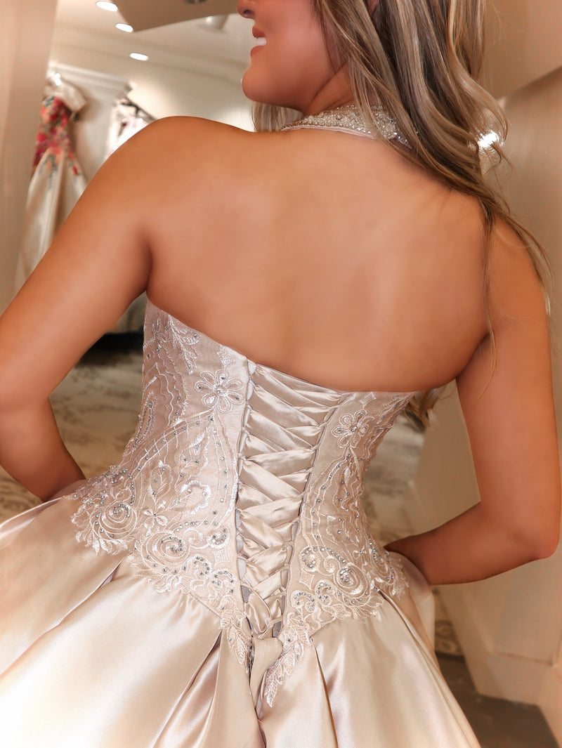 Back of Model in this absolutely stunning champagne colored ball gown featuring a halter neckline and beautiful embroidery on the bodice and skirt! A lace-up back of easy up or downsizing, matching bolero jacket and pockets complete this fabulous look! And it's at Rsvp Prom and Pageant, your source for the HOTTEST bridal, Prom and Pageant Dresses, Quince and Exclusive Evening Gowns, located in Atlanta, Georgia!