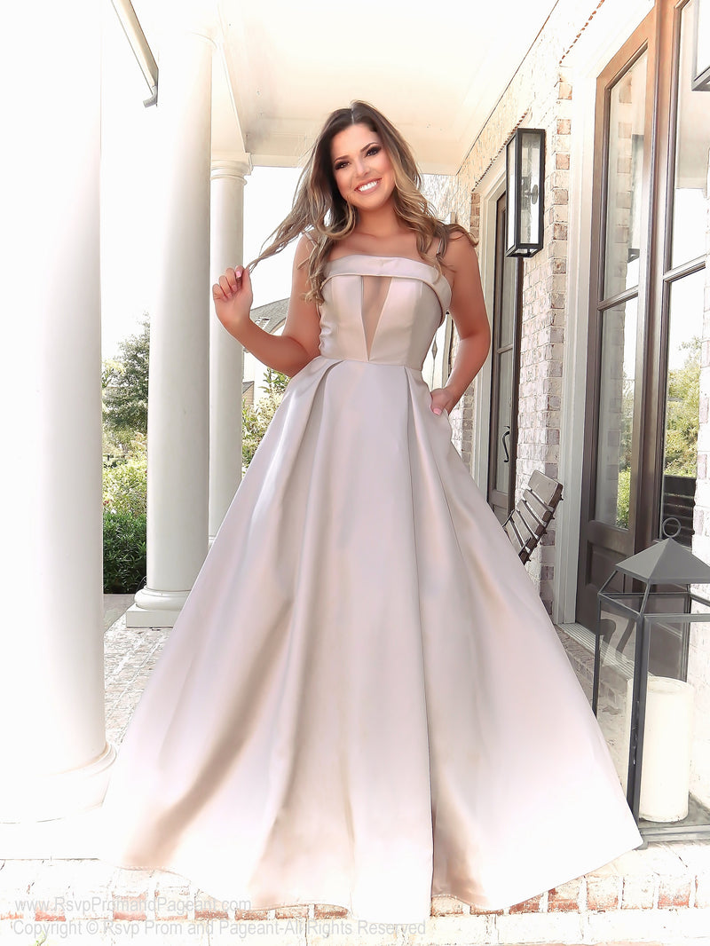 Brunette in this simple and elegant ball gown featuring pockets and a v neckline! And it's at Rsvp Prom and Pageant, your source for the HOTTEST Prom and Pageant Dresses and Exclusive Evening Gowns and located in Atlanta, Georgia!