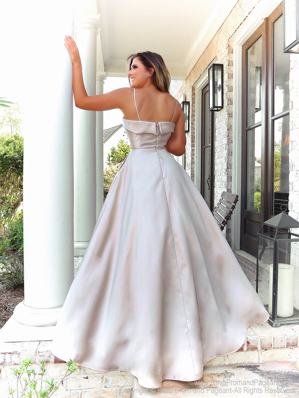 Back of Brunette in this simple and elegant ball gown featuring pockets and a v neckline! And it's at Rsvp Prom and Pageant, your source for the HOTTEST Prom and Pageant Dresses and Exclusive Evening Gowns and located in Atlanta, Georgia!