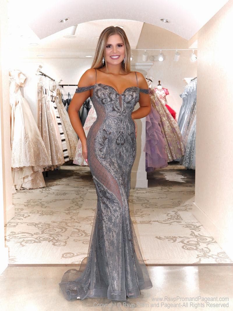 Model in a spectacular gunmetal over nude evening gown featuring illusionary clear sides without showing skin! Extremely sophisticated and elegant!  And it's at Rsvp Prom and Pageant, your source for the HOTTEST Prom and Pageant Dresses and exclusive evening gowns and located in Atlanta, Georgia!