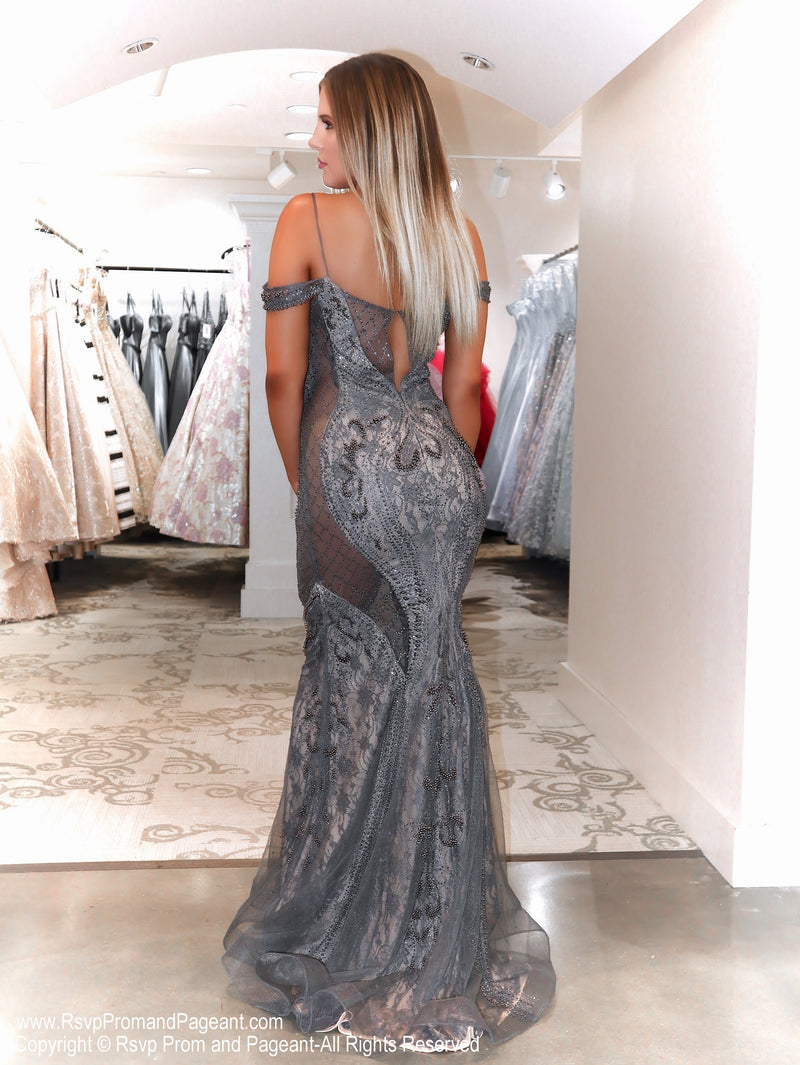 Back of Model in a spectacular gunmetal over nude evening gown featuring illusionary clear sides without showing skin! Extremely sophisticated and elegant!  And it's at Rsvp Prom and Pageant, your source for the HOTTEST Prom and Pageant Dresses and exclusive evening gowns and located in Atlanta, Georgia!