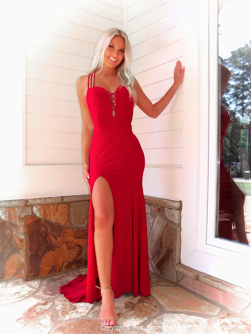 Model in a fabulous red dress featuring a plunging v neckline, a slit and a crisscross strappy open back. And it's at Rsvp Prom and Pageant, your source for the HOTTEST Prom and Pageant Dresses and exclusive evening gowns and located in Atlanta, Georgia!