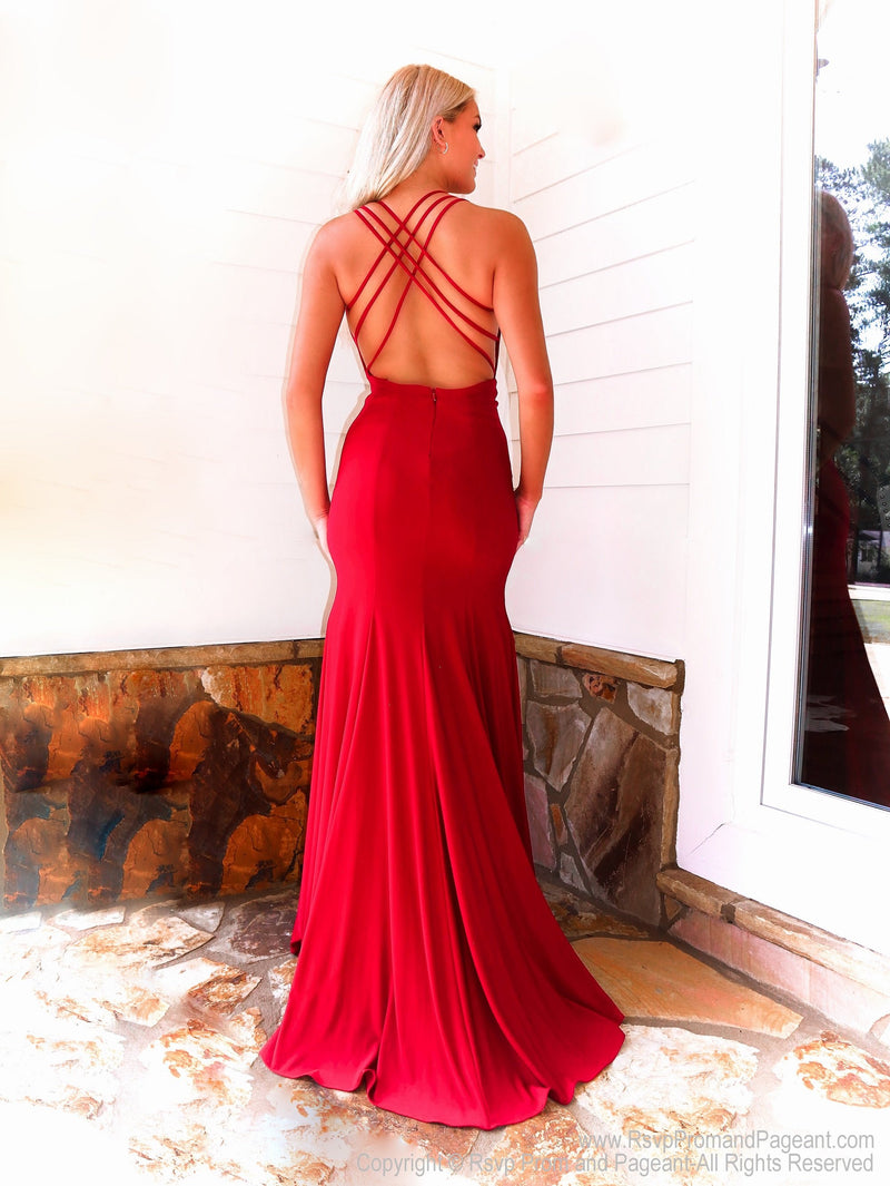 Back of model in a fabulous red dress featuring a plunging v neckline, a slit and a crisscross strappy open back. And it's at Rsvp Prom and Pageant, your source for the HOTTEST Prom and Pageant Dresses and exclusive evening gowns and located in Atlanta, Georgia!
