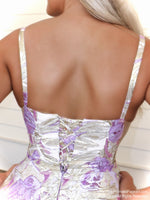 Closeup of back of model in the sweetest ball gown with its high neckline and a floral pattern all over the full skirt! And it's at Rsvp Prom and Pageant, your source for the HOTTEST Prom and Pageant Dresses and Exclusive Evening Gowns and located in Atlanta, Georgia!