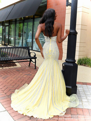 Back of African American model looking absolutely stunning in this yellow mermaid evening gown with silver accents and a sweetheart neckline! The mermaid silhouette features a fully crinoline line skirt and a long train for drama! And it's at Rsvp Prom and Pageant, your source for the HOTTEST Prom and Pageant Dresses and exclusive evening gowns and located in Atlanta, Georgia!