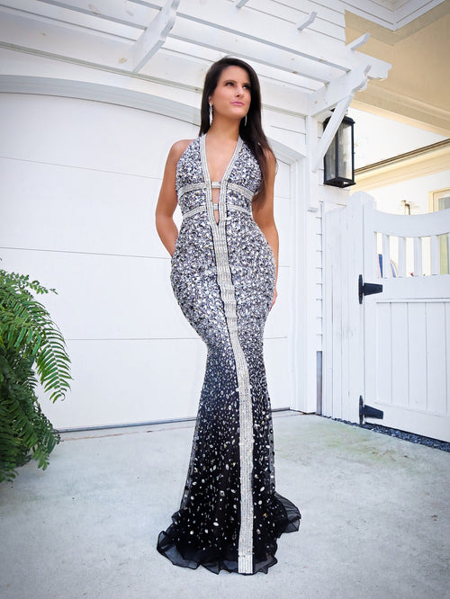 Model wowing the crowd in this gorgeous black evening gown fully detailed with iridescent stones! It also features a low cut back and a halter neckline! And it's at Rsvp Prom and Pageant, your source for the HOTTEST Prom, Pageant and exclusive evening gowns and located in Atlanta, Georgia!