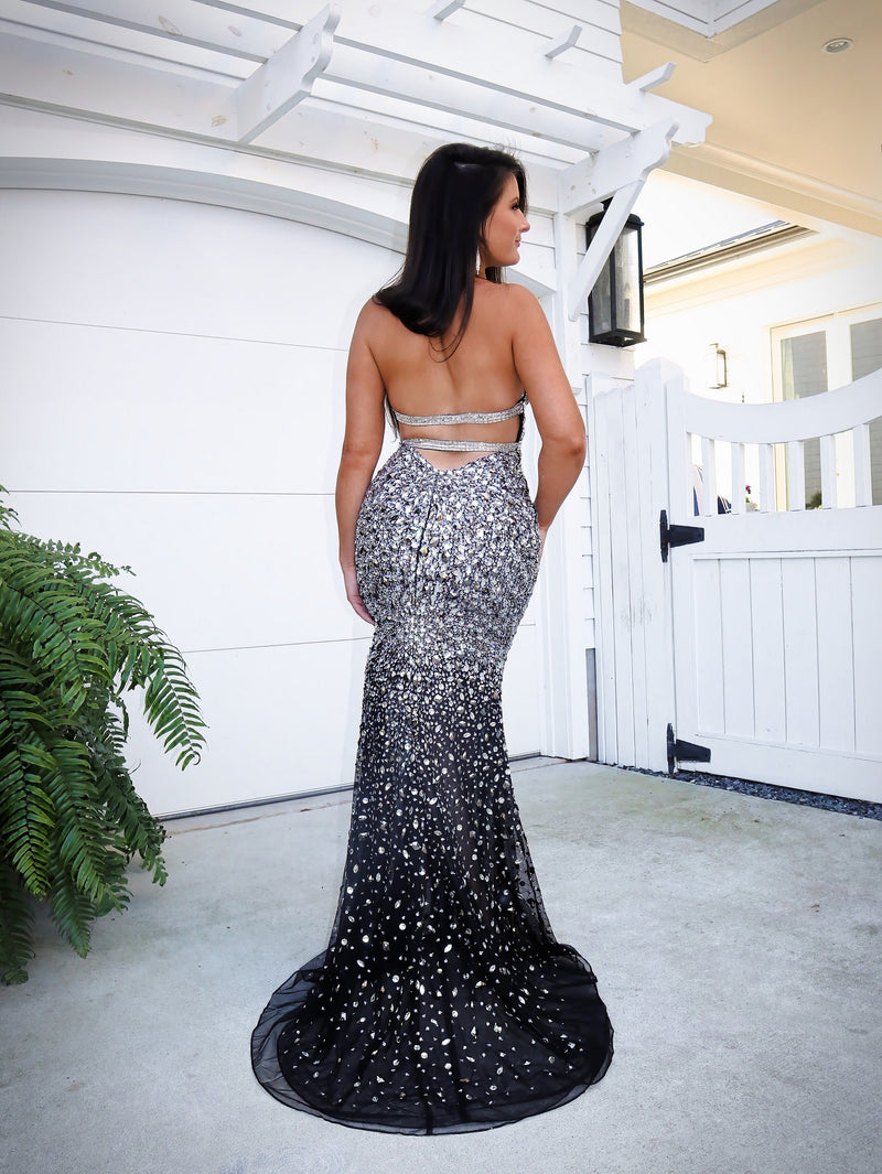 Back of Beautiful Model wowing the crowd in this gorgeous black evening gown fully detailed with iridescent stones! It also features a low cut back and a halter neckline! And it's at Rsvp Prom and Pageant, your source for the HOTTEST Prom, Pageant and exclusive evening gowns and located in Atlanta, Georgia!