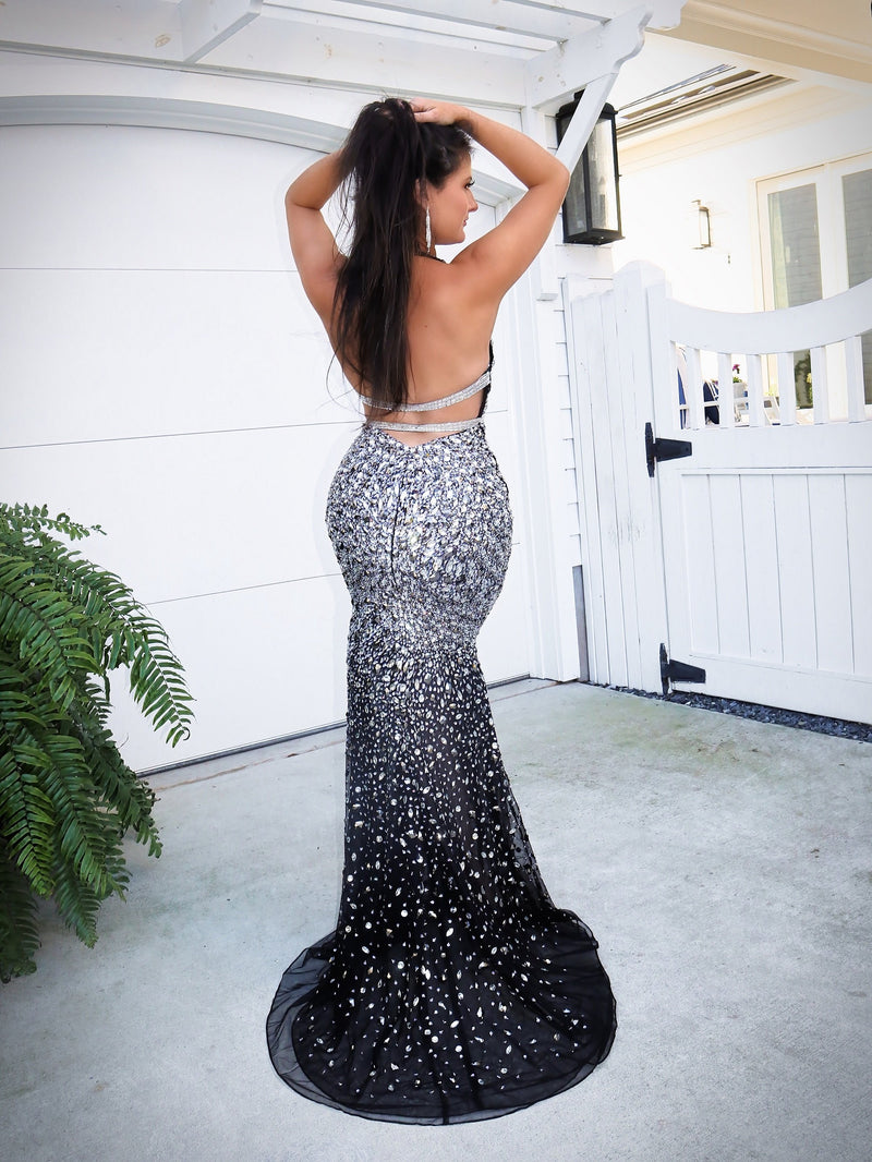 Back of Model wowing the crowd in this gorgeous black evening gown fully detailed with iridescent stones! It also features a low cut back and a halter neckline! And it's at Rsvp Prom and Pageant, your source for the HOTTEST Prom, Pageant and exclusive evening gowns and located in Atlanta, Georgia!