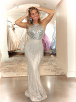 Model in this Nude, glittering evening gown featuring a halter top embellished with mirrored stones and an open back. The skirt covered fringes which wil definitely win you the crown! Perfect for prom, pageant or any formal! And it's at Rsvp Prom and Pageant, your source for the HOTTEST Prom and Pageant Dresses and Exclusive Evening Gowns and located in Atlanta, Georgia!