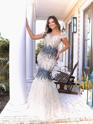 Model in this Nude/Gunmetal mermaid gown featuring feathered fringe around the shoulders and feathers on the skirt! This off the shoulder look with stunning beading and layered colors is the perfect dress to wow the crowd! And it's at Rsvp Prom and Pageant, your source for the HOTTEST Prom and Pageant Dresses and exclusive evening gowns and located in Atlanta, Georgia!