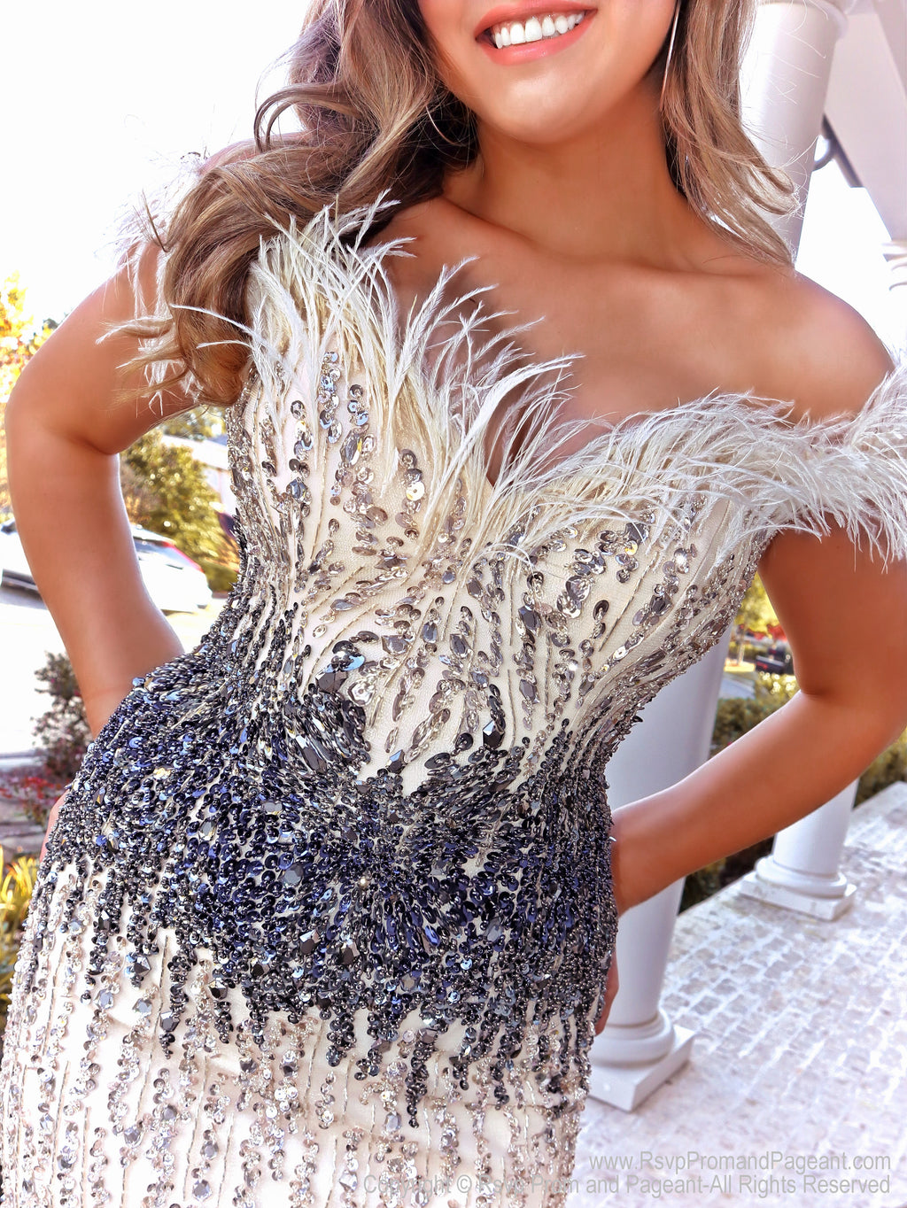 Closeup of Model in this Nude/Gunmetal mermaid gown featuring feathered fringe around the shoulders and feathers on the skirt! This off the shoulder look with stunning beading and layered colors is the perfect dress to wow the crowd! And it's at Rsvp Prom and Pageant, your source for the HOTTEST Prom and Pageant Dresses and exclusive evening gowns and located in Atlanta, Georgia!