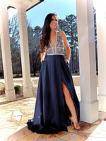 This navy gown is to die for with its AB stone adorned v-neck that dips into a beautiful navy satin skirt with an open slit to show off your legs and pockets! And it's at Rsvp Prom and Pageant, your source for the HOTTEST Prom and Pageant Dresses and Exclusive Evening Gowns located in Atlanta, Georgia!