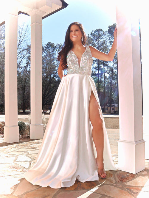 Beautiful model in this Ivory gown with beaded top, a V neckline, a slit, Shorts and pockets!  And it's at Rsvp Prom and Pageant, your source for the HOTTEST Prom and Pageant Dresses and exclusive evening gowns and located in Atlanta, Georgia!