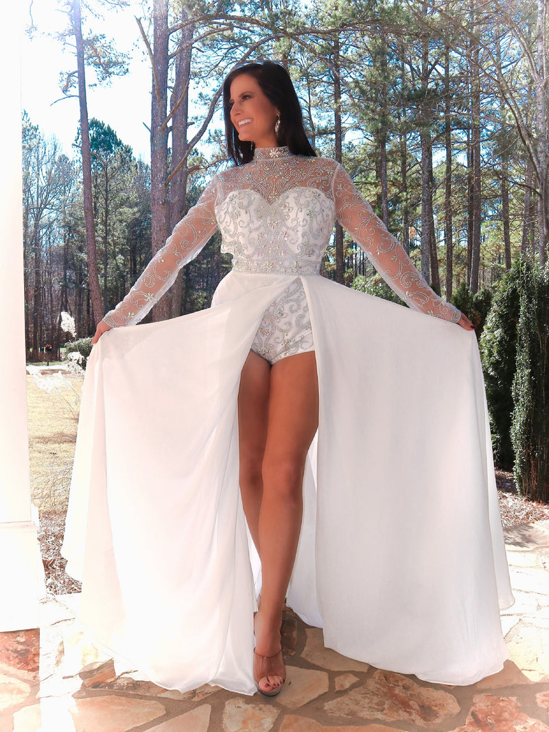 Pretty model in this phenomenal beaded bodysuit gown! The bodysuit is adorned with an intricate beaded design; and it has long sleeves, a high neckline, and an open back! Over the bodysuit is an ivory flowing chiffon skirt with a slit! This gown is goddess level! And it's at Rsvp Prom and Pageant, your source for the HOTTEST Prom and Pageant Dresses and Exclusive Evening Gowns and located in Atlanta, Georgia!