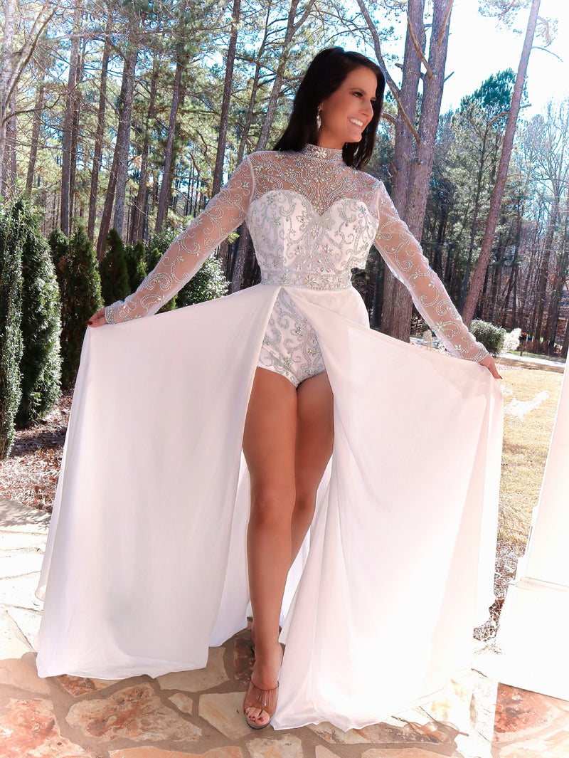 beautiful model in this phenomenal beaded bodysuit gown! The bodysuit is adorned with an intricate beaded design; and it has long sleeves, a high neckline, and an open back! Over the bodysuit is an ivory flowing chiffon skirt with a slit! This gown is goddess level! And it's at Rsvp Prom and Pageant, your source for the HOTTEST Prom and Pageant Dresses and Exclusive Evening Gowns and located in Atlanta, Georgia!