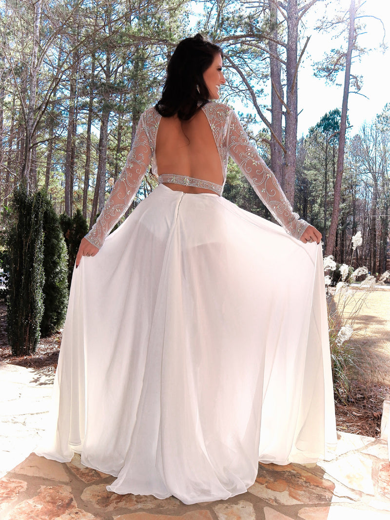 Back of pretty model in this phenomenal beaded bodysuit gown! The bodysuit is adorned with an intricate beaded design; and it has long sleeves, a high neckline, and an open back! Over the bodysuit is an ivory flowing chiffon skirt with a slit! This gown is goddess level! And it's at Rsvp Prom and Pageant, your source for the HOTTEST Prom and Pageant Dresses and Exclusive Evening Gowns and located in Atlanta, Georgia!