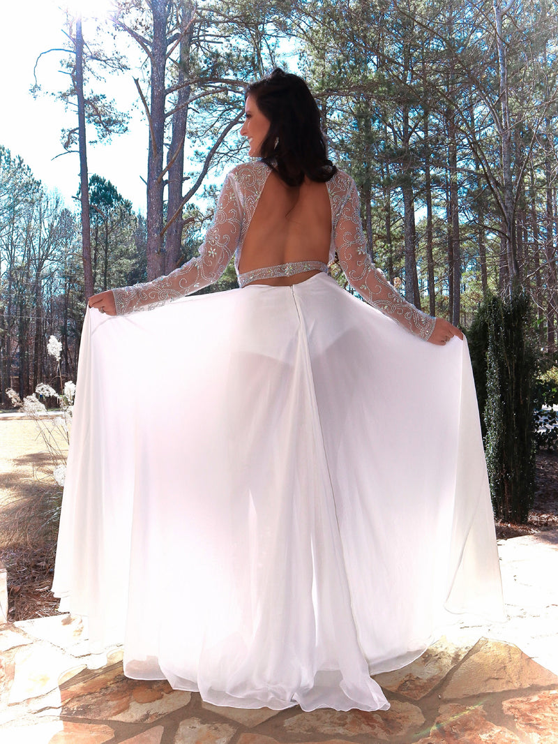 Back of brunette model in this phenomenal beaded bodysuit gown! The bodysuit is adorned with an intricate beaded design; and it has long sleeves, a high neckline, and an open back! Over the bodysuit is an ivory flowing chiffon skirt with a slit! This gown is goddess level! And it's at Rsvp Prom and Pageant, your source for the HOTTEST Prom and Pageant Dresses and Exclusive Evening Gowns and located in Atlanta, Georgia!