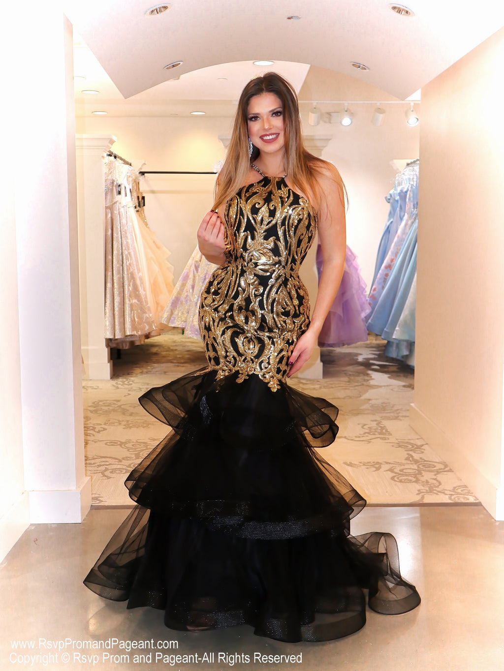 "Model in this runway ready Black/Gold mermaid dress that will have everyone saying ""WOW!!"". This gown features a striking sequin design, halter neckline, and layered tulle flair! And it's at Rsvp Prom and Pageant, your source for the HOTTEST Prom and Pageant Dresses and Exclusive Evening Gowns and located in Atlanta, Georgia!"