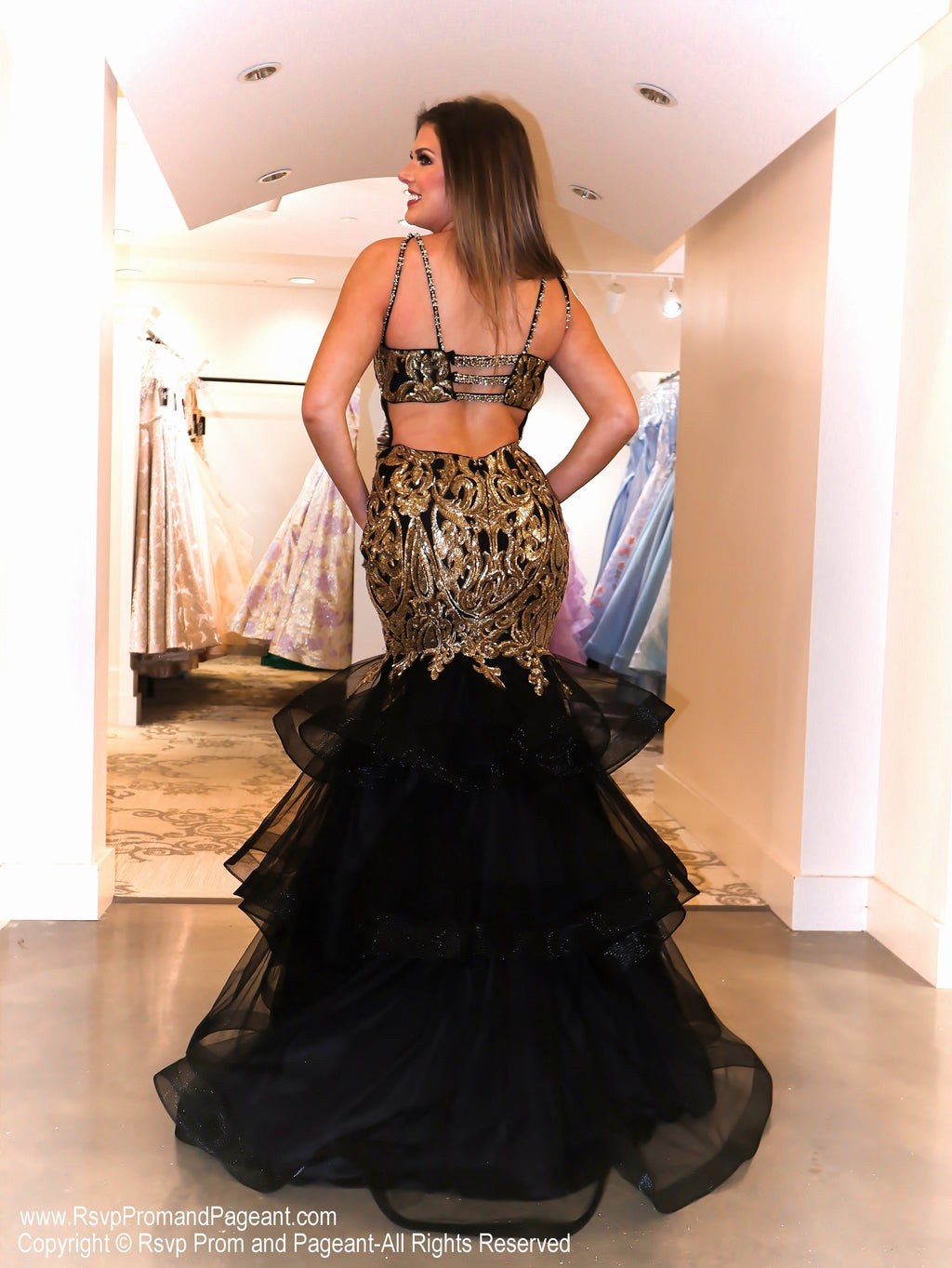 "Back of Model in this runway ready Black/Gold mermaid dress that will have everyone saying ""WOW!!"". This gown features a striking sequin design, halter neckline, and layered tulle flair! And it's at Rsvp Prom and Pageant, your source for the HOTTEST Prom and Pageant Dresses and Exclusive Evening Gowns and located in Atlanta, Georgia!"