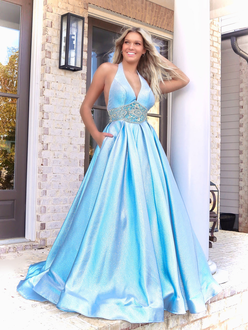Model looking and feeling like a princess in this stunning light blue ball gown featuring a Halter Neckline and pockets! And it's at Rsvp Prom and Pageant, your source for the HOTTEST Prom and Pageant Dresses and Exclusive Evening Gowns and located in Atlanta, Georgia!
