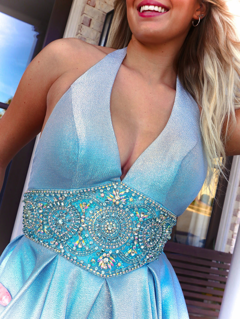 Closeup of Model looking and feeling like a princess in this stunning light blue ball gown featuring a Halter Neckline and pockets! And it's at Rsvp Prom and Pageant, your source for the HOTTEST Prom and Pageant Dresses and Exclusive Evening Gowns and located in Atlanta, Georgia!