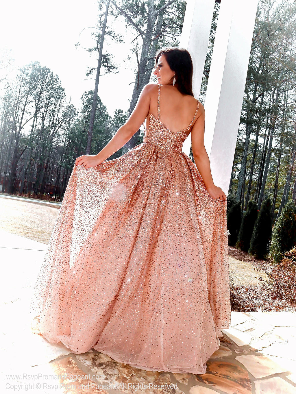 Back of Model in this Rose Gold ball gown which is the definition of Prom Heaven!! The ombre sequins, open sides, sparkling beading, and beautiful color will have you beaming all night!  And it's at Rsvp Prom and Pageant, your source for the HOTTEST prom and pageant dresses and Exclusive Evening Gowns and located in Atlanta, Georgia!