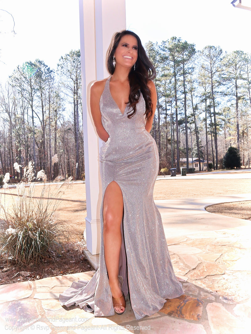 Model in a nude prom dress featuring a plunging v neckline, slit, open strappy back and glitter everywhere. Perfect for PROM! And it's at Rsvp Prom and Pageant, your source for the HOTTEST Prom and Pageant Dresses and exclusive evening gowns and located in Atlanta, Georgia!